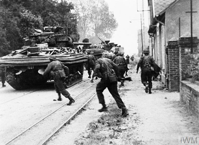 Les chars Sherman DD de l'escadron B, les 13 et 18e Royal Hussars soutiennent les commandos du 4e commando de la 1re Brigade de Service spécial, rue de Riva-Bella, lorsqu'ils se rendent à Ouistreham, région de Sword, le 6 juin 1944. © IWM